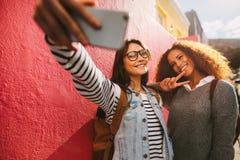 带selfie出去的女朋友在他们的天 免版税库存图片