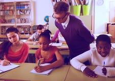 帮助非裔美国人的学生的老师在教室 库存图片