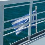 希腊的旗子小船的后方的 库存照片