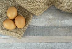 布朗在粗麻布的鸡鸡蛋在木背景 库存图片