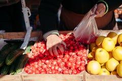 市场获取的萝卜的卖主买家的 免版税图库摄影