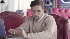 帅哥与在现代咖啡馆关闭的膝上型计算机一起使用 时髦的确信的商人移动他的在节奏的身体  股票录像