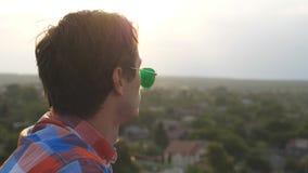 帅哥档案站立在屋顶和敬佩美丽的景色的太阳镜的在平衡时间 休息年轻的人和 股票视频