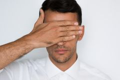 帅哥盖子眼睛特写镜头画象用在灰色背景隔绝的手 可爱的商人蒙住眼睛的保护 免版税图库摄影