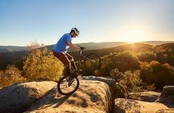 平衡在试验自行车的后面轮子的运动员骑自行车者 免版税图库摄影