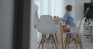 幸福家庭年轻美丽的母亲和两个儿子画与坐在桌上的色的铅笔在厨房里 的treadled 股票录像