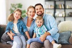 幸福家庭母亲父亲和孩子在家在长沙发 免版税库存图片