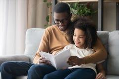 幸福家庭黑色父亲和孩子女儿读书故事书 免版税库存图片