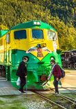 2018年9月15日-史凯威,AK:走在白色通行证铁路引擎96,百老汇St前面的两个女性步行者 免版税库存图片