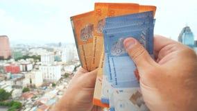 年轻人在他的手上详述马来西亚的金钱以吉隆坡为背景的市中心 影视素材