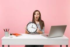 年轻人拿着圆的闹钟的震惊困惑的妇女,当在有被隔绝的个人计算机膝上型计算机的办公室工作坐粉红彩笔时 图库摄影