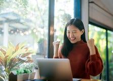 年轻亚裔女孩庆祝成功或愉快的姿势与膝上型计算机 图库摄影