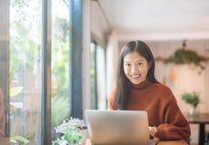 年轻亚裔女孩庆祝成功或愉快的姿势与膝上型计算机 免版税库存图片