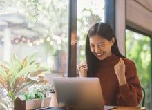 年轻亚裔妇女庆祝成功或愉快的姿势与膝上型计算机 免版税库存照片