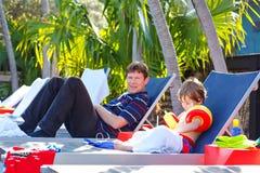 年轻休息在游泳场附近的父亲和他的小儿子 人和小学龄前孩子男孩游泳floaties做的 免版税库存图片