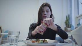 年轻俏丽的女孩画象有红色修指甲盐的她的坐在舒适餐馆的可口胃口盘 股票录像