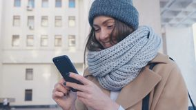 年轻可爱的妇女特写镜头画象时髦的成套装备的检查智能手机室外在城市背景 股票视频