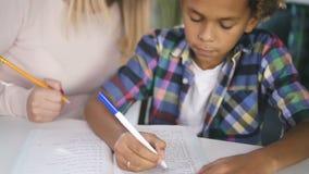 年轻可爱的母亲帮助给有家庭作业问题的儿子 股票录像