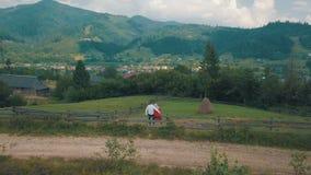 年轻夫妇一起骑墙观望在山附近 夏天多云天气 从空气的射击 股票视频