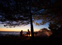 年轻夫妇男人和妇女有休息在旅游帐篷和灼烧的营火在海岸在森林附近 库存照片