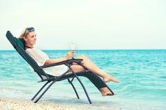 年轻女人坐在躺椅和饮用的酒的海滩 库存图片
