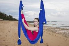 年轻女人实践的飞行瑜伽asana户外 健康,体育,瑜伽概念 免版税图库摄影