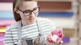 年轻女人工作她的膝上型计算机和电话在花店 包裹在纸的愉快的卖花人妇女花在花 股票视频