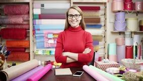年轻女人工作她的膝上型计算机和电话在花店 包裹在纸的愉快的卖花人妇女花在花 股票录像