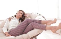 年轻女人在一把舒适的椅子放松 库存照片