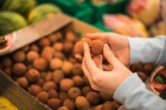 年轻女人在超级市场选择新鲜的lychee 库存照片
