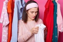 年轻女人在陈列室里拿着新的衬衣,选择在机架的衣裳 夫人有在衬衣的孔 翻倒女性发现在白色女衬衫的污点 免版税库存照片