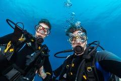 年轻女人和人做selfie的轻潜水员 图库摄影