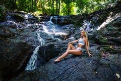 年轻女人摆在小瀑布 图库摄影