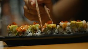 年轻女人手用棍子采取寿司 中国棍子寿司卷的概念在一块黑暗的板材的 影视素材