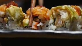 年轻女人手用棍子采取寿司 中国棍子寿司卷的概念在一块黑暗的板材的 股票录像