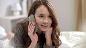 年轻女人谈话在手机在床上 电话微笑的联系的妇女 影视素材