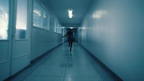 年轻女人跑远离她的沿一个黑暗的走廊的追求者 影视素材