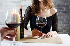 年轻女人饮用的红酒在一个日期在餐馆 免版税库存照片