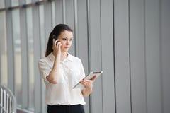 年轻女实业家谈话在手机,当支持窗口在办公室时 美好的年轻女性模型在办公室 免版税图库摄影
