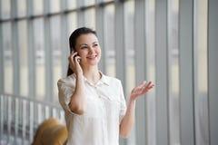 年轻女实业家谈话在手机,当支持窗口在办公室时 美好的年轻女性模型在办公室 免版税库存图片