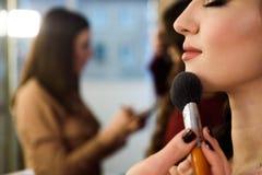 年轻女性模型秀丽和健康干净的皮肤  应用与刷子的妇女粉末基础 免版税库存图片
