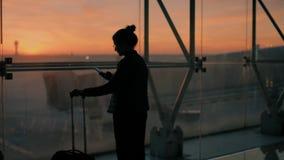 年轻女性旅客在早飞行的机场 股票录像
