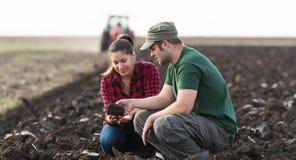 年轻农夫检查土,当拖拉机犁领域时 免版税库存照片