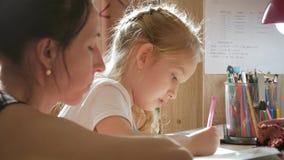 年轻母亲帮助她的有她的家庭作业的女儿在桌上上在灯的光下 股票视频