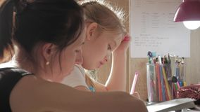年轻母亲帮助她的有她的家庭作业的女儿在桌上上在灯的光下 影视素材