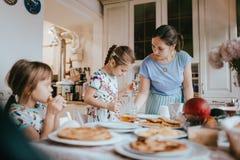 年轻有同情心的吃薄煎饼用蜂蜜的母亲和她的两个小女儿在早餐在舒适厨房里 免版税图库摄影