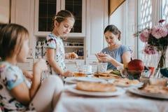 年轻有同情心的母亲和她的两个小女儿食用一顿早餐在有大窗口的轻的厨房 免版税库存照片