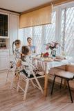 年轻有同情心的母亲和她的两个小女儿食用一顿早餐在有大窗口的轻的厨房 库存图片