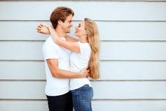 年轻时尚时髦的夫妇在城市的街道上站立夏令时 免版税库存图片