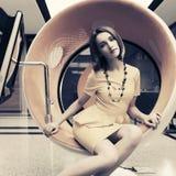 年轻时装业妇女坐计算机椅子在办公室 免版税库存照片